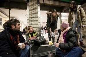 deux filles proposent un trou de beigne à l'itinérant didi rencontré à la station atwater alors qu'il discute avec Maxime et un bénévole de l'organisme exeko. (crédit photo : Adil Boukind)