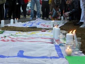 À la fin de l'événement, chaque personne a pu déposer des bougies auprès des drapeaux commémoratifs. Crédit photo : Anastassia Depauld
