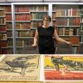 Marie-Josée Lapalme devant des affiches de la Première Guerre mondiale de la collection de la BLRCS. Jusqu'à son entrée en fonction en juillet dernier, les tâches dont elle est maintenant chargée étaient assurées de manière sporadique par des employés temporaires. Crédit : Jacob Côté