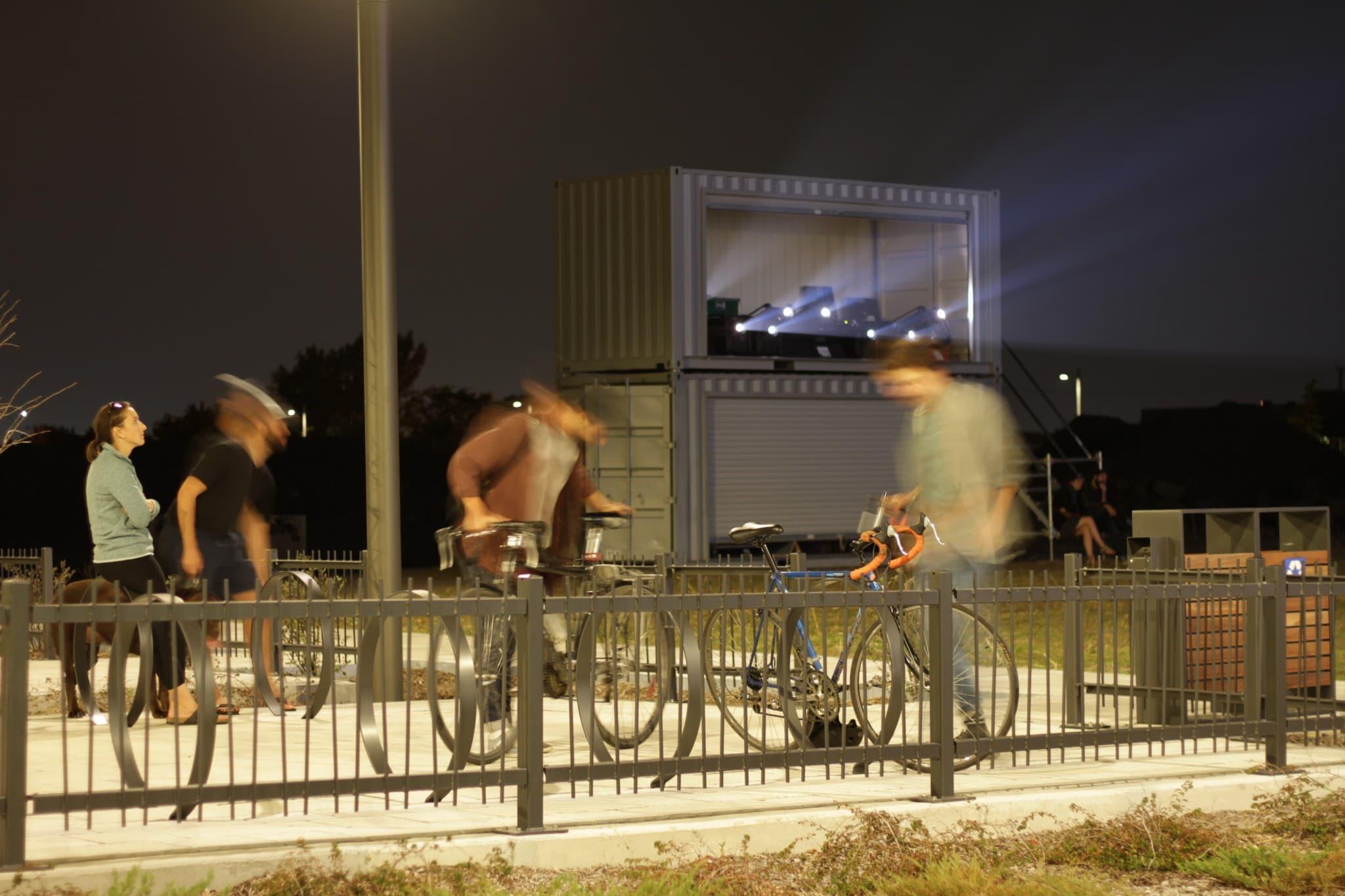 Des spectateurs s'apprêtent à quitter le site après avoir observé les vidéos étudiantes, projetées en boucle sur le mur extérieur de l'édifice voisin. Crédit : L-P. Pontbriand