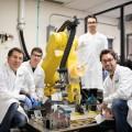 Un système robotisé de 1,7 mètre est utilisé pour réaliser le dépôt de matériaux composites sur une pièce de moteur d'avion. Photo : Jacob Côté.