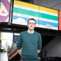 Le Directeur des affaires institutionnelles de la TOHU, Pablo Maneyrol, devant un escalier et une passerelle faits de panneaux récupérés de l'arène d'auto-tamponneuses de l'Expo 67. Photo : Jacob Côté